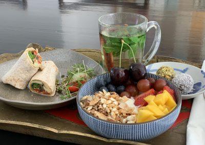 Vegan ontbijt: wrap gegrilde groenten en hummus, granola bowl met vers fruit, choco-dadelballen